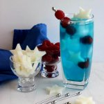 Patriotic Passion Cocktail is tall and blue with small white jicama stars and red raspberries sitting alongside and in the cocktail too.