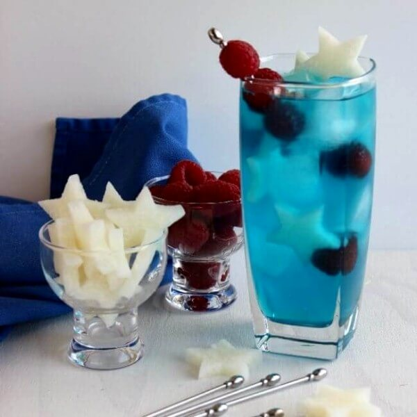 Patriotic Passion Cocktail is tall and blue with small white jicama stars and red raspberries sitting alongside a navy cloth napkin.