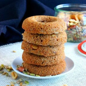 Baked Trail Mix Cake Donuts are stacked five high. Light golden brown and sitting on a white plate with hints of pumpkin seeds and nuts peeking out. A jar of trail mix sits behind.