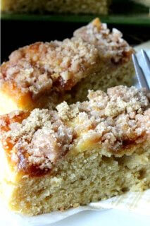 Vegan Coffee Cake with Apple Cinnamon Streusel is cut into two rectangles with a very up-close and personal photo of the sweet temping cinnamon streusel and moist coffee cake.