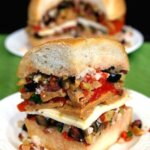 Vegan Muffuletta Sandwich is layers of mixed olives, roasted bell pepper, sliced seitan and dairy free cheese. Close-up front triangle wedge that shows all the layers.