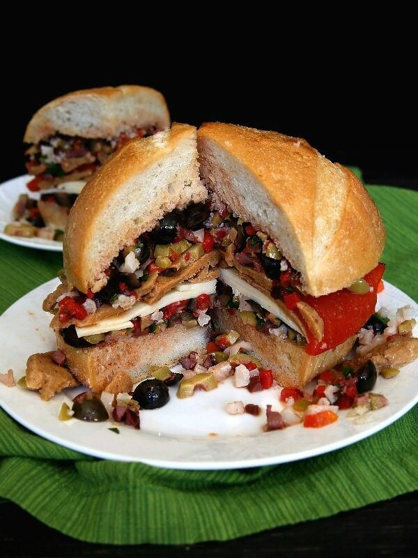 Vegan Muffuletta Sandwich is layers of mixed olives, roasted bell pepper, sliced seitan and dairy free cheese. Photo of a round loaf and a wedge cut out to view all of the layers inside.