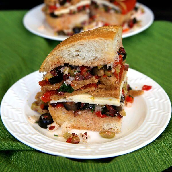Vegan Muffuletta Sandwich is layers of mixed olives, roasted bell pepper, sliced seitan and dairy free cheese. Side wedge slice spilling out onto the white plate and just waiting for a big bite.