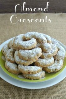 Almond Crescents are stacked with their crescent moon shapes all facing inward to form a cookie mountain. Sitting on a lime green polka dot plate.