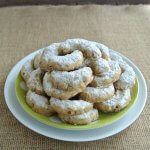 Almond Crescents are stacked with their crescent moon shapes all facing inward to form a cookie mountain. Sitting on a lime green and white polka dot plate and there's a white plate under that.