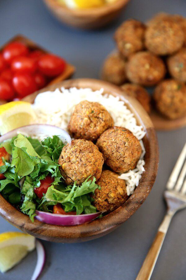 Baked Lentil Balls with Zesty Rice are piled in a wooden bowl next to a green salad and rice. Cherry tomatoes and more lentil balls are piled in bowls behind.