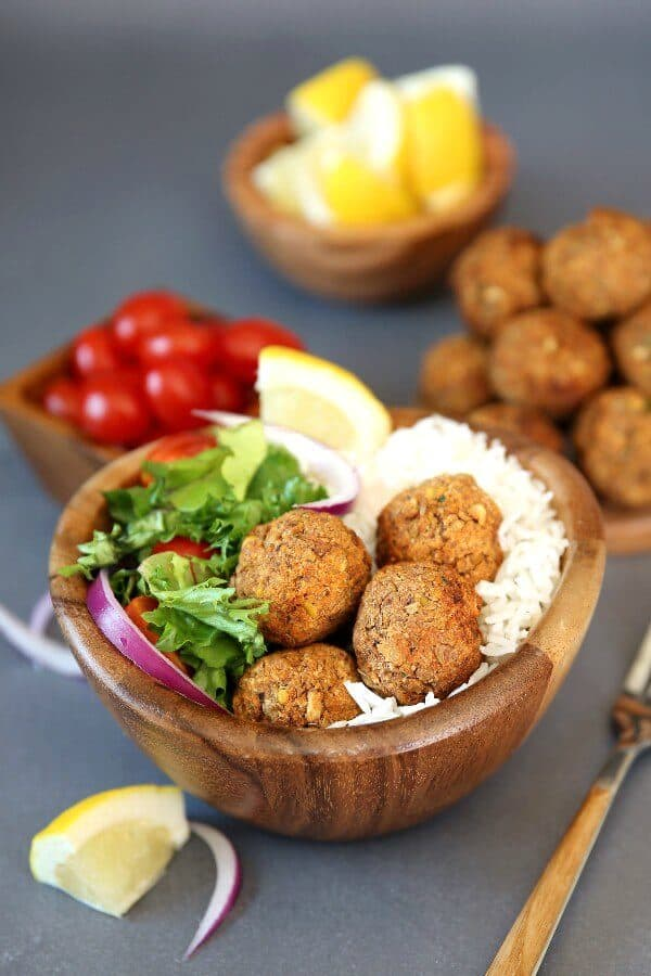 Baked Lentil Balls with Zesty Rice are piled in a wooden bowl next to a green salad and rice. Lemon slices and red onion slivers add color.