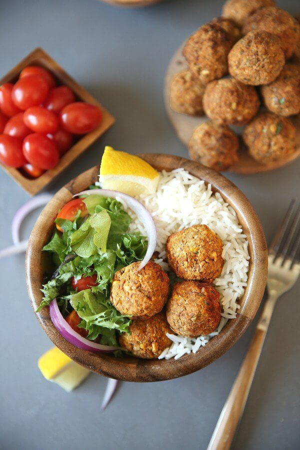 Baked Lentil Balls with Zesty Rice are piled in a wooden bowl next to a green salad and rice. Lemon slices and red onion slivers add color. Looking down from above.