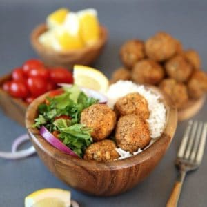 Baked Lentil Balls with Zesty Rice are piled in a wooden bowl next to a green salad and rice. Lemon slices, red onion slivers and cherry tomatoes add color.