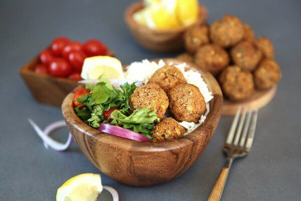 Baked Lentil Balls with Zesty Rice are piled in a wooden bowl next to a green salad and rice. Lemon slices and red onion slivers and a fork are also included.