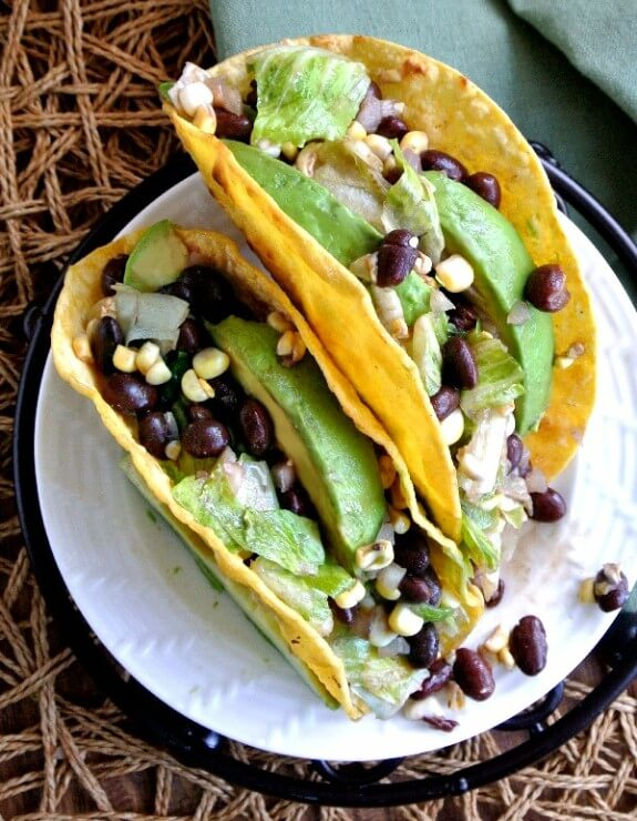 Corn and Black Bean Salsa Tacos are two to a plate with an overhead view. The shells are overflowing with green, yellow and black beans. White plate is sitting on a black trivet.