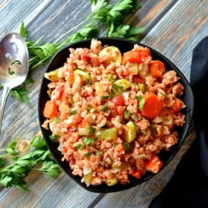 Garden Vegetable Rice Pilaf is is sharing a black bowl with green, red and orange vegetables. Sprinkled with fresh parsley and photographed centered from overhead.