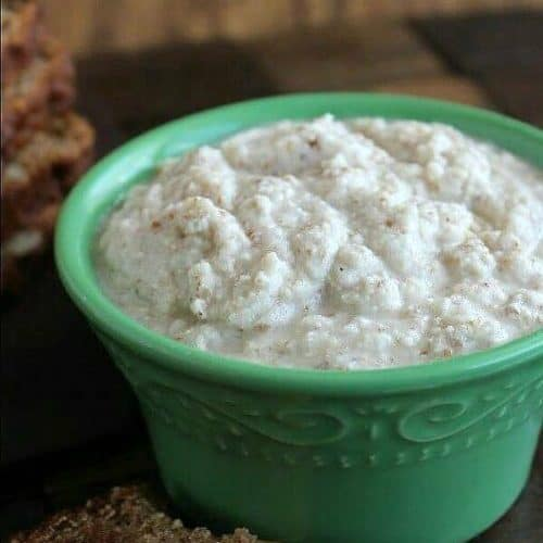 Homemade Almond Mayonnaise is in a small green bowl with some 'mayo' slathered on pear bread.