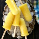 Pineapple Kiwi Popsicles are laying on a bed of ice in a silver tray. Five bright yellow popsicles and pointing every which way.