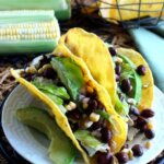 Corn and Black Bean Salsa Tacos are two to a plate and tilted forward. The shells are overflowing with green, yellow and black beans. White plate is sitting on a black trivet.