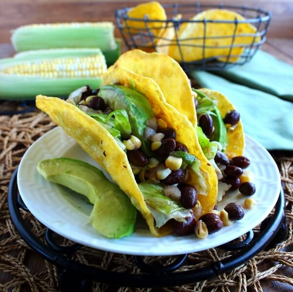Corn and Black Bean Salsa Tacos are two to a plate and overflowing with green, yellow and black beans. Two more ears of corn and taco shells are in the background.