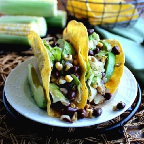 Corn and Black Bean Salsa Tacos are two to a plate and overflowing with green, yellow and black beans. White plate is sitting on a black trivet.