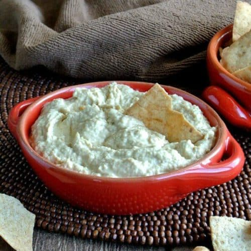 Baba Ghanoush Dip is loaded in a red handled bowl with p-ita chip poking inside and waiting to be scooped up. Sitting on a chocolate beaded mat.