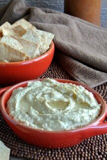 Baba Ghanoush Dip is loaded in a red handles bowl with a swirl of extra virgin olive oil on the top. Sitting on a chocolate beaded mat.