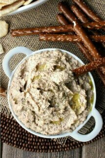Best Kalamata Hummus is an overhead photo and looking down at piled high hummus in a flat handled bowl and drizzled with extra virgin olive oil and fresh herbs