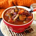 Best Vegan Chili Recipe with Mushrooms is tilted forward in a bright red bowl and has an orange handled spoon scooping up a bite.