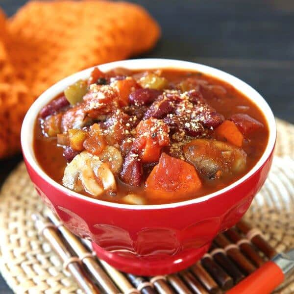 Best Vegan Chili Recipe with Mushrooms is front and center in a bright red bowl and has an orange handled spoon laying along side on a chocolate brown bamboo trivet.