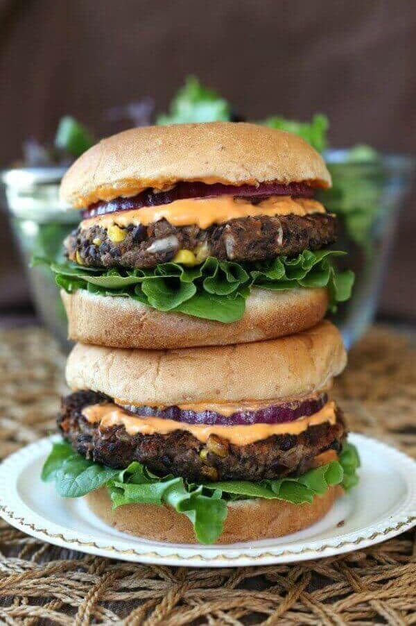 Black Bean Burgers Recipe has to fully dressed burgers stacked two high on top of each other. Little bits of carrots, corn and onion are peeking out of the patties.