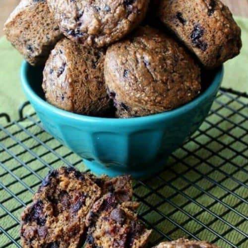 Black Forest Cherry Muffins are piled high in a turquoise bowl> It's sitting on a cooling rack with more muffins in front with one broken open.