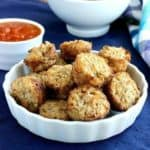 Cauliflower Pizza Bites are little mini muffins and are piled high in a white scalloped bowl on a cobalt blue placemat. Pizza sauce and a blue checked napkin on the side.