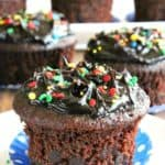 Easy Chocolate Cupcakes with one front and center. Chocolate chips peeking out of the sides of the cupcake and it's sitting on a blue and white paper polka dot muffin cup.