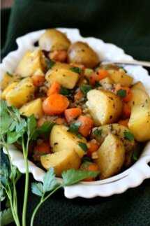 Carrots and potatoes in a white bowl with juices.