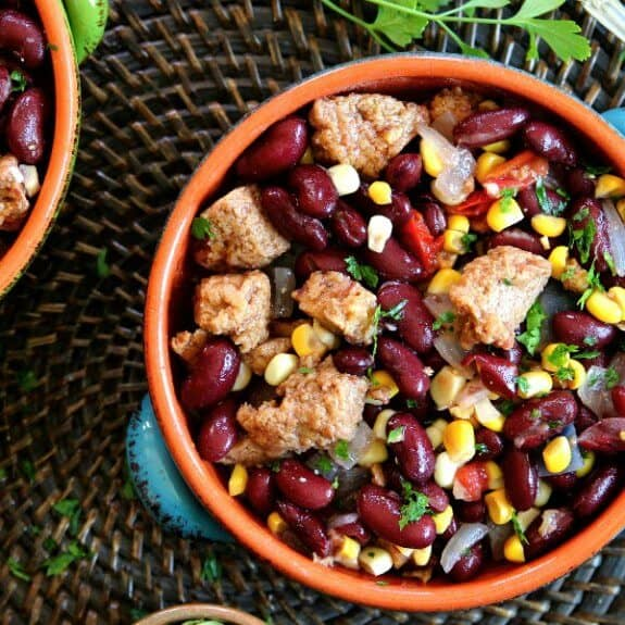 Mexican Cassoulet Recipe with Plant Based Sausage as an overhead photo with bright color veggies in a turquoise handled bowls, cropped on the edges and sitting on a chocolate mat.