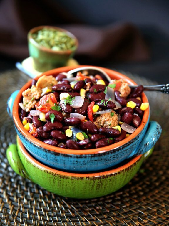 Mexican Cassoulet Recipe with Plant-Based Sausage is piled high and tilted forward in a turquoise pottery bowl but is also sitting in a matching bright lime green pottery bowl.