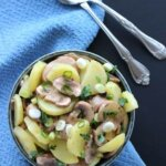 Mushroom Potato Salad being seen from overhead. Thick slices of potatoes and mushrooms are sprinkled with scallion slices all on a blue background.