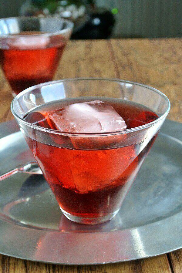 Pomegranate Swizzle is bright red and showing through a flared glass with a giant ice cube floating inside. Sitting on a pewter tray.