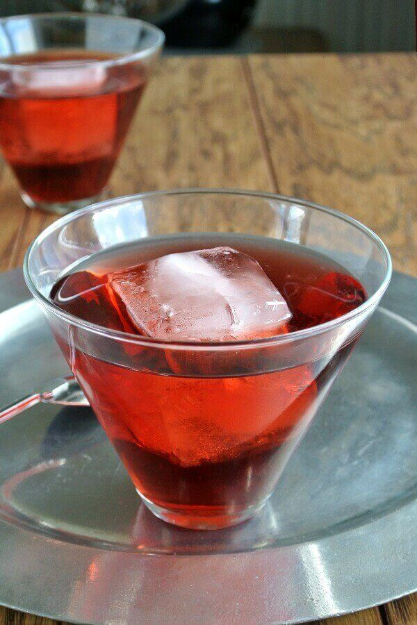 Pomegranate Swizzle is bright red and showing through a flared glass with a giant ice cube floating inside. One is sitting behind too. very elegant on a round pewter tray.