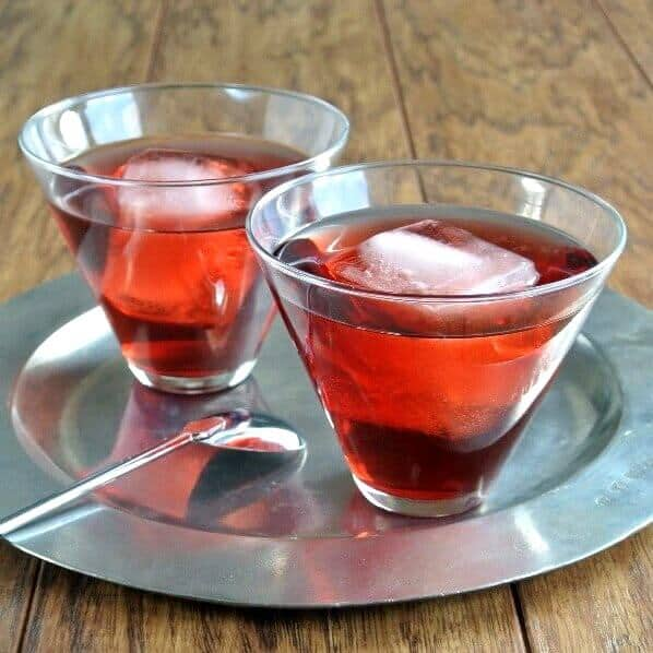Pomegranate Swizzle is bright red and showing through two flared glasses with a giant ice cube floating inside each. Sitting on a pewter tray.