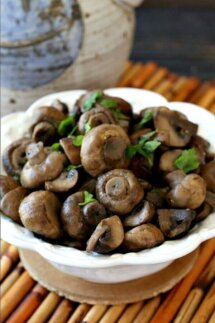 Slow Cooker Balsamic Glazed Mushrooms are in a while scalloped bowl sitting on cork coaster and bamboo mat.