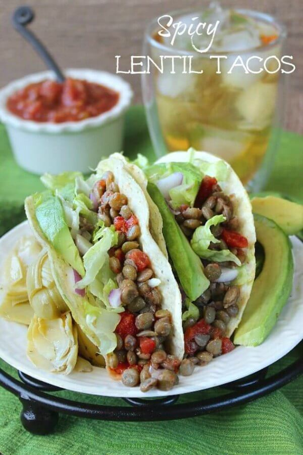 Spicy Lentil Tacos are sitting on a white plate and a lovely lentil mixture is spilling out onto the plate. Avocado and artichoke hearts are on each side.
