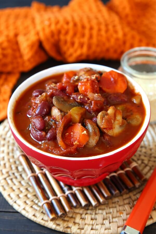 Best Vegan Chili Recipe with Mushrooms is tilted forward in a bright red bowl and has an orange handled spoon laying along side.
