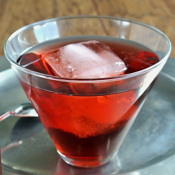Pomegranate Swizzle is bright red and showing through a flared glass with a giant ice cube floating inside. Sitting on a pewter tray with a silver swizzle spoon sitting next to it.