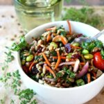 Superfood Salad with Maple Vinaigrette has every color of the rainbow in deep rich shades. It's all in a white bowl with fresh herbs in front on the granite slab.