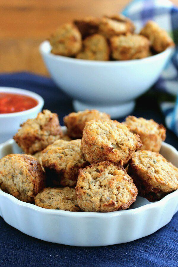 Cauliflower Pizza Bites are little mini muffins and are piled high in a white scalloped bowl on a cobalt blue placemat. Pizza sauce in a small bowl on the side.