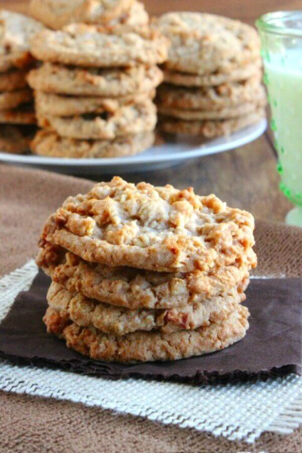 Apple Pie Cookies are golden brown and stacked 4 cookies high on a chocolate brown napkin and an ivory burlap square.