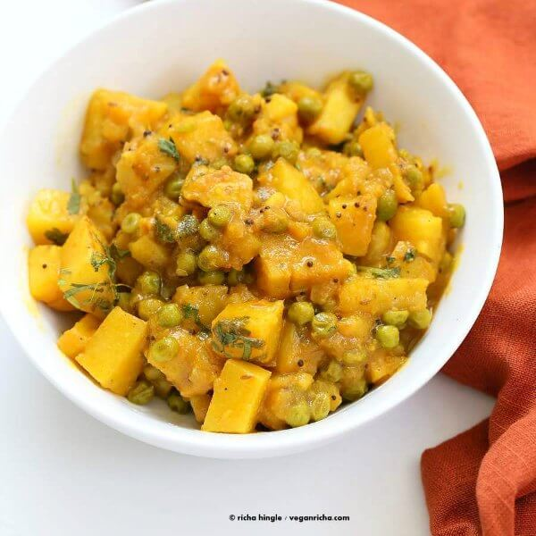 Bombay Potatoes and Peas are viewed from above and it's served in a small white bowl with an orange cloth on the side.