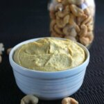 Cashew Cheddar Cheese Spread is golden and in a white rimmed bowl on black.