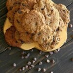 Chocolate Chip Banana Bread Cookies are being seen from overhead and there is a stack on a wooden board also on top of a picnic table. Chocolate chips are scattered on the table.