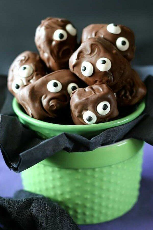 Copycat Almond Joy Candy Bars are piled in a green jar with their googly eyes looking at you. Swirly chocolate hair and mouths are in scary and cute poses just for Halloween.