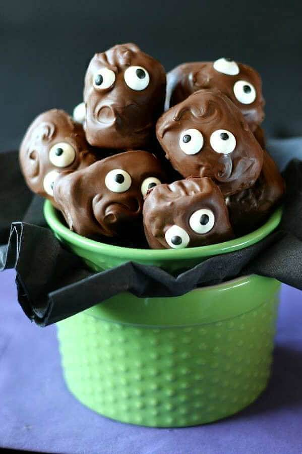 Copycat Almond Joy Candy Bars are piled in a green jar with their googly eyes looking at you. Swirly chocolate hair and mouths are in scary and cuts poses.