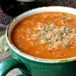 Couscous Minestrone Soup is an deep orange in color and it fills a giant green mug. Tilted forward with parmesan cheese and fresh herbs sprinkles on top.
